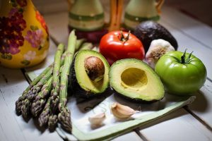 A picture of asparagus, avocado, an apple and tomato
