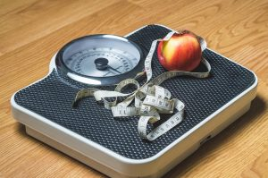 A picture of scales with an apple and a tape measure