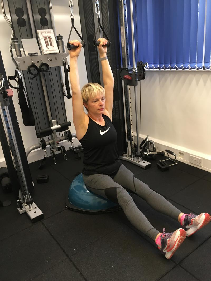 Weight training will transform you. A lady doing resistance training. Performing lat pulldown