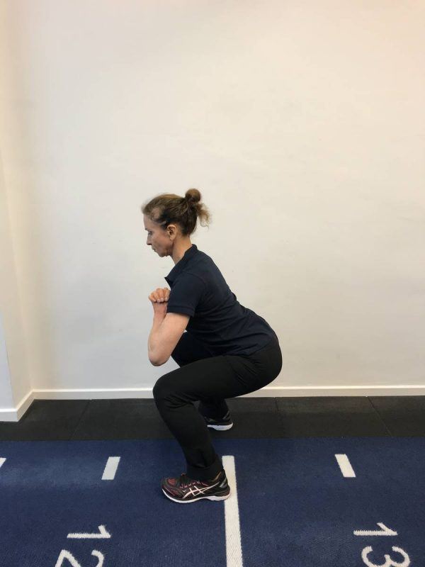 At home legs bums and tums. Coach doing bodyweight squats